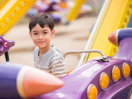 jeune fille: Petit garçon dans le parc d'attractions