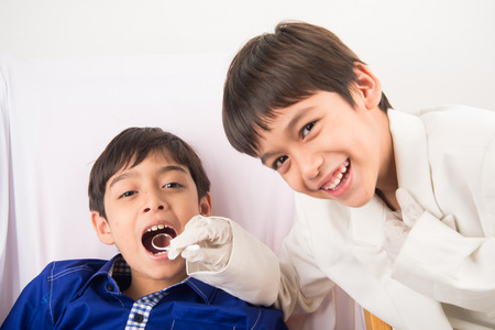 pretend: Little sibling boy pretend as a dentist vLittle sibling boy pretend as a dentist close up inside mouth check up