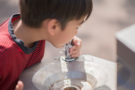 thirst: Little boy drinking public water in the park Stock Photo