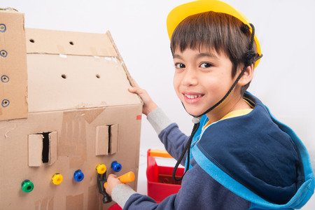 pretend: Little boy pretend as a mechanic use tools fix the paper house Stock Photo