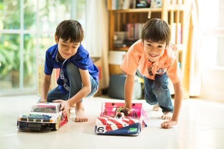 Kleine broer of zus jongen die stuk speelgoed auto ras bij elkaar binnen