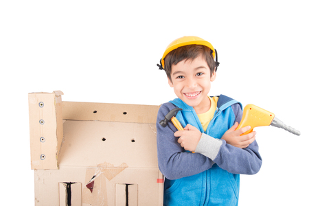 funny boy: Little boy pretend as a mechanic use tools fix the paper house Stock Photo
