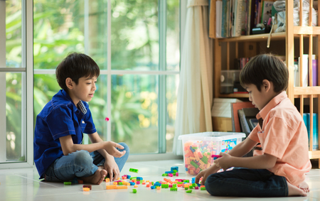 kid playing: Little sibling  boy playing block indoor house education Stock Photo