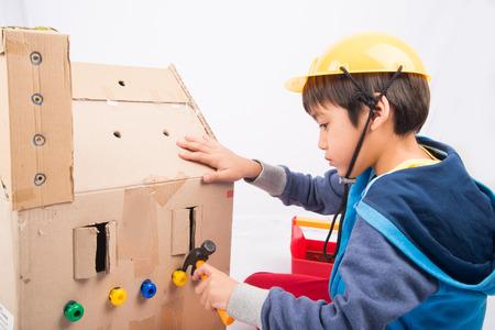 pretend: Little boy pretend as a mechanic use tools fix the paper house Stock Photo