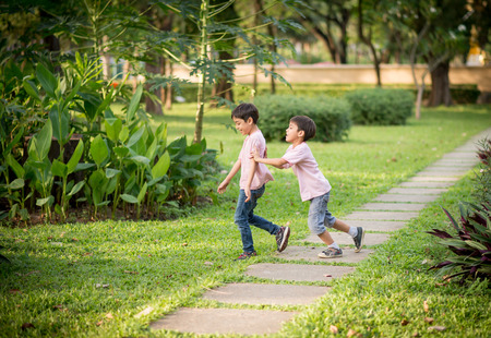Little sibling boy playing together in the park Stock Photo