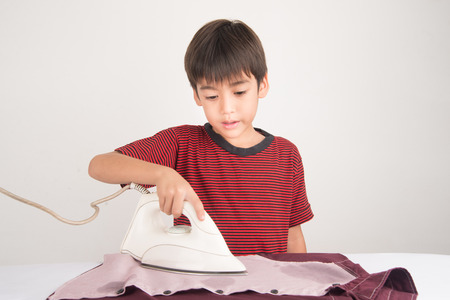 laborious: Little boy ironing house work