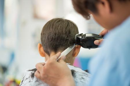 Niño sentado para el corte de pelo en la barbería Foto de archivo
