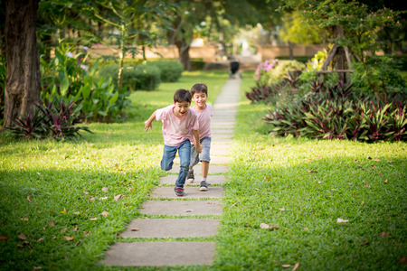 Little sibling boy playing together in the park Archivio Fotografico