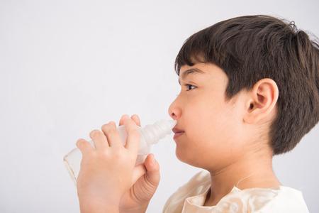 Weinig jongen die zout water gebruikt om zijn neus schoon te maken Stockfoto