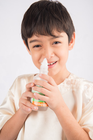 nasal drops: Little boy using salt water to clean his nose Stock Photo