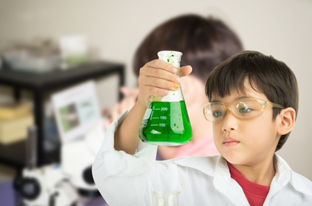 eminent: Little boy learning in chemecal in science in class