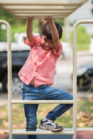 taking risks: Little boy playing at playground climbing