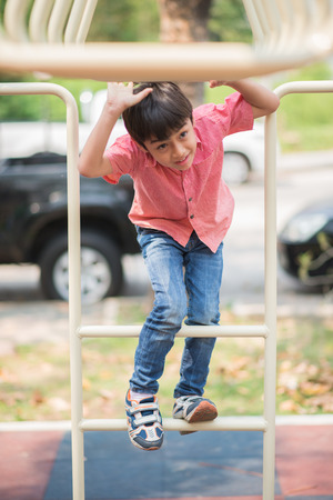 jungle gyms: Little boy playing at playground climbing