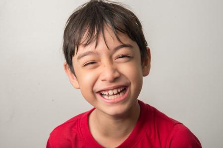 Kleiner Junge Mischungsverhältnis auf grauem Hintergrund mit glücklichen Gesicht lachen
