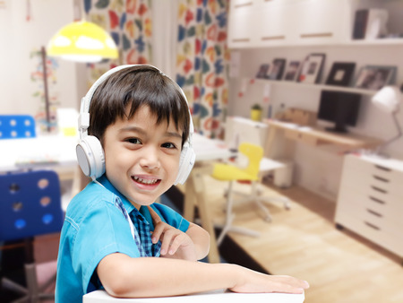 Little boy with headset doing homework in the room Standard-Bild