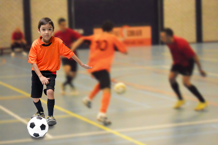 Little boy kicking football soccer ball indoor gym Archivio Fotografico