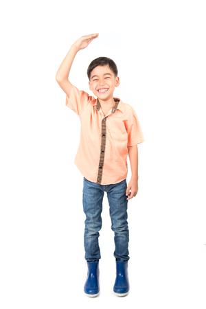 Kleiner Junge seine Höhe auf weißem Hintergrund überprüft