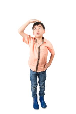 Kleiner Junge checkin seine Höhe auf weißem Hintergrund