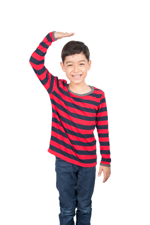 tallness: Little boy checking his height on white background