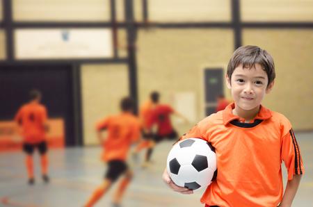 풋살 체육관에서 축구를 들고있는 어린 소년 스톡 콘텐츠