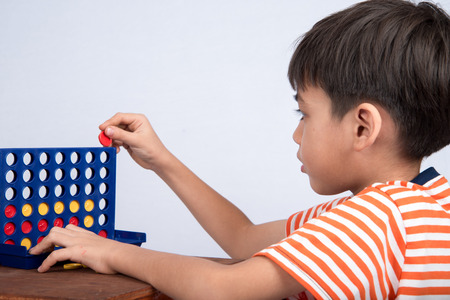Little boy playing connect four game soft focus at eye contact