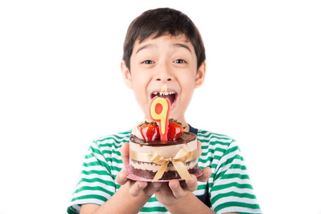 funny boy: Little boy blowing candle on the cake for his birthday Stock Photo
