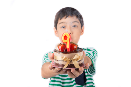 Little boy browing candle on the cake for his birthday Stock Photo