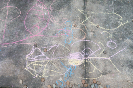 family outside: Little boy drawing and coloring by chalk on the ground