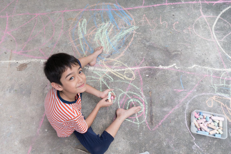 kid drawing: Little boy drawing and coloring by chalk on the ground