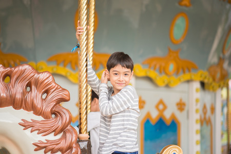 marry go round: Little boy sitting in marry go round in amusement park