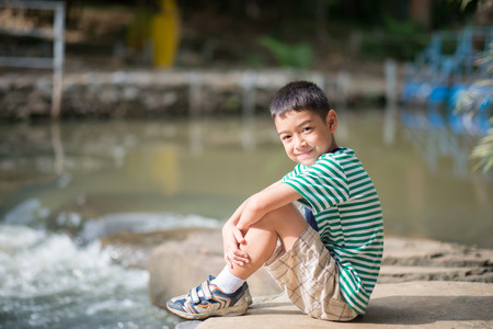 Little boy sitting on the rock looking at waterfall alone color spot Stock Photo