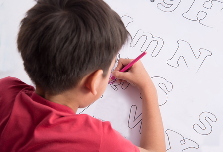 asian children: Little child boy painting and coloring alphabet  in the paper indoor activities Stock Photo