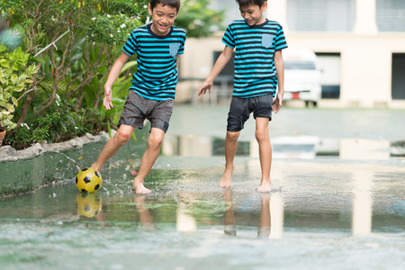 logging: Little boy kicking ball in the water logging on the street