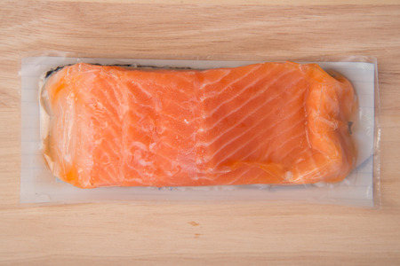 departmentstore: piece of Fresh salmon in package on wood background
