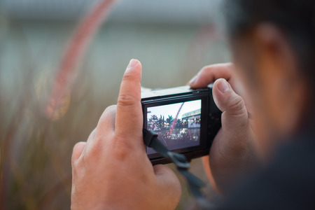 snapping fingers: Close up of man hand taking picture by digital camera Stock Photo