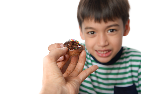 ignore: Little boy ignore to to eat sweet chocolate from allergy  Stock Photo
