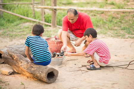 Asain Father and son making barbecue togheter outdoor activity Stock Photo
