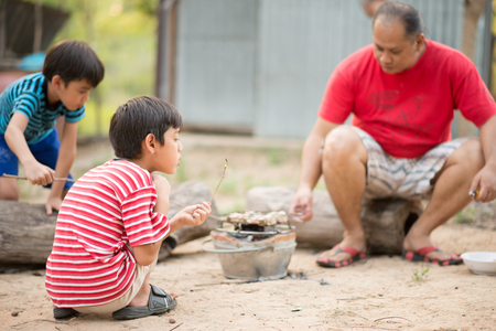 Asain Father and son making barbecue togheter outdoor activity