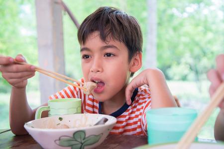 Little boy eating noodle at resturant