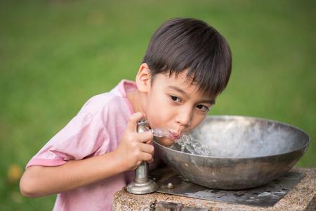 Little asian boy drinking water in the public park