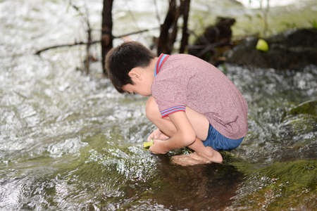 Littl boy playing at waterfall with happy and smile outdoor activeites with family Stock Photo