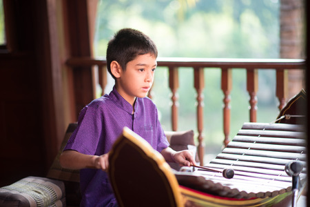 Little asian Thai boy playing alto xylophone music performance in ceremony