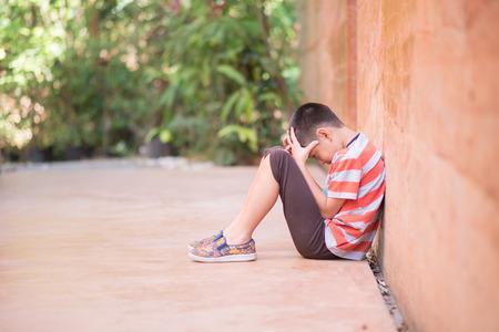 Little boy sitting alone with sad feeling  Фото со стока