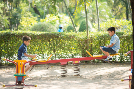 Little sibling boys playing seesaw at playground
