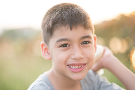 Portrait close up of little boy smiling happy in the park