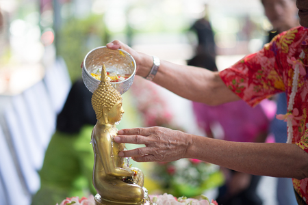 People gently pour the water on the torso or the hands of the Buddha statue.