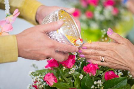 The younger traditionally sprinkle water onto their parents and grandparents hands Stock Photo