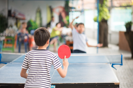Bambino che gioca a ping pong all'aperto con la famiglia Archivio Fotografico