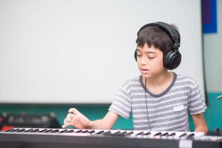 Asian little boy play piano  study music classroom Stock Photo