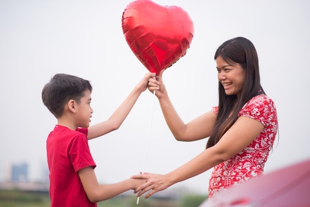 Little boys giving balloon heart to his mother with love Standard-Bild